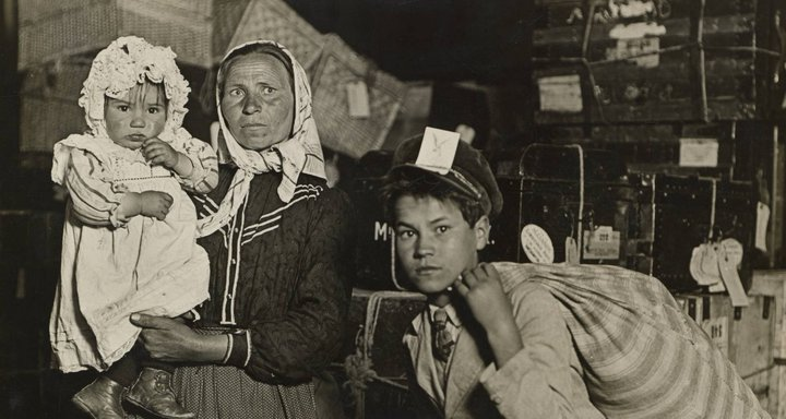Immigrant Family in the Baggage Room of Ellis Island - Lewis W. Hine, 1905 - public domain